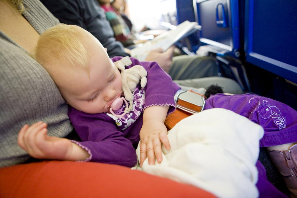 Baby asleep in an aeroplane seat tips for flying with babies and toddlers