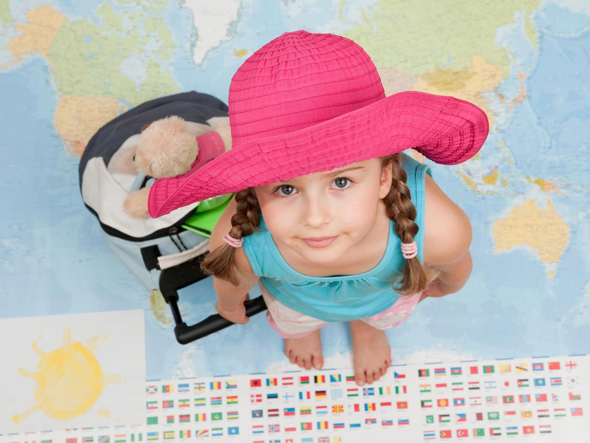 travel with child little girl in a pink hat with a suitcase