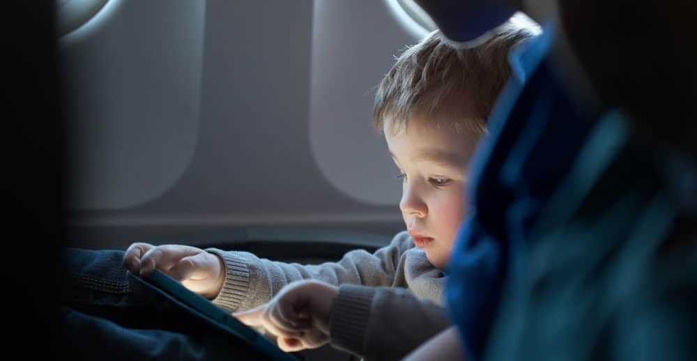 Little boy on a plane engrossed in an ipad