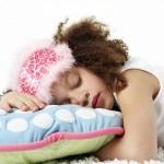 Girl sleeping on a colourful cushion