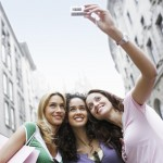 Three women friends taking a photo of themselves. Make new friends to help cope with culture shock.