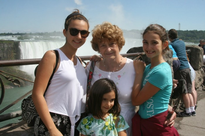 Three young girls and grandmother photographed in front of Niagra Falls