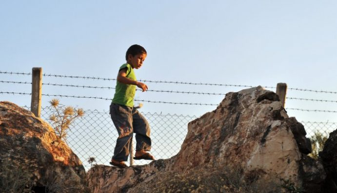 Child playing near a barbed wire fence