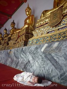 Golden statues of Buddha looking over a sleeping baby
