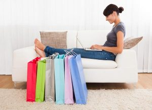 shop online for delivery outside of the uk. Woman on a white sofa with colourful shopping bags